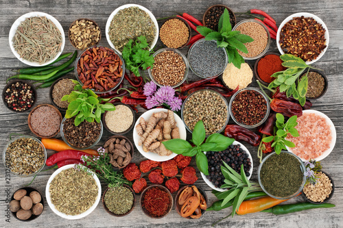 Large herb and spice food selection dried and fresh on rustic wood background. With chilli pepper varieties including dried ring of fire, padron and scorpio. Top view.
