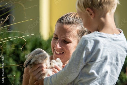 Happy young mother holding cute furry pet rabbit - 231247478