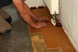 Worker laying parquet flooring. Worker installing wooden laminate flooring. - 231249417