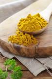 Currypulver auf einem Holzlöffel - 231249829