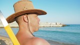 A man in a cowboy hat at a resort. A man on the beach on a chaise longue. - 231255894