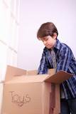 Boy packing his toys in a cardboard box - 231264094