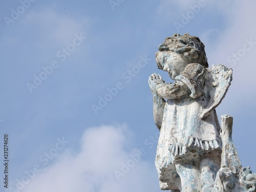 Stone statue of a little angel with wings, praying. Statue damaged by time. In the background, the blue sky. Faith. There is room for text. - 231274620