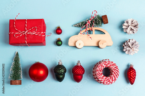 Leinwanddruck Bild Set of Christmas decorations on blue background. Wooden toy car with Christmas tree on the roof, gift box and other baubles.