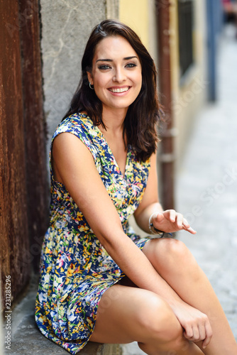 Poster Happy young woman with blue eyes smiling sitting on urban step.