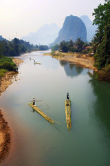 people rowing on bamboo raft in asian river  © MICHEL