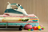Iron on a stack of cotton fabric. Sewing clothes or bed linen made from cotton fabric. A pile of cloth, iron, ironing board, thread and needles on the table.