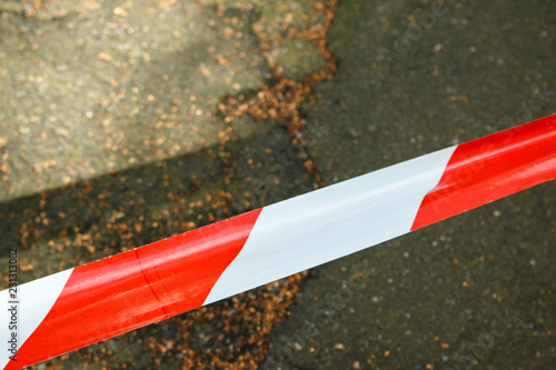 striped red-white warning ribbon on the asphalt background. red and white ribbon on asphalt background. © Микола Чурпіта