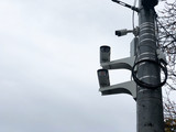 Cameras on the road pole. Three CCTV surveillance cameras on a pole. City cctv security surveillance camera system attached on the traffic light pole with gray sky background.