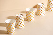 Golden polka dot paper cup isolated on beige background