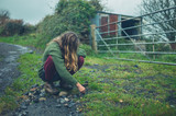 Young woman sitting on country road - 231329204
