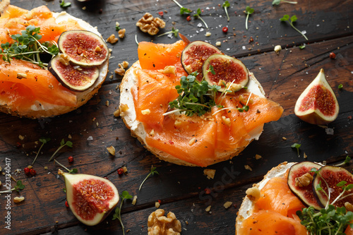 Leinwandbild Motiv Salmon Bagel Sandwich with figs, cress salad, walnuts, cream cheese and grain on rustic wooden background. healthy breakfast
