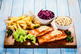 Grilled salmon with french fries and vegetables served on cutting board on wooden table - 231346264