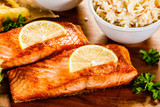 Grilled salmon with french fries and vegetables served on cutting board on wooden table - 231346481
