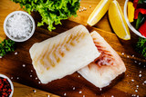 Fresh raw cod with herbs and vegetables served on cutting board on wooden table - 231346890