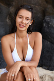 Photo of slim of attractive Caucasian dark haired woman, has slim perfect body, wears white swimsuit, sits near cliff background, has relaxed expression. Vertical shot of pleasant looking girl outdoor - 231361426