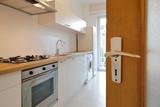 porte ouvrant sur petite cuisine d'appartement - 231371880