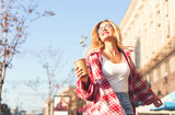 Smiling beautiful blonde womam walking at the street, holding cup of coffee. - 231377458