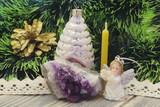 Christmas holidays. Golden pine cone, Christmas tree toy, wax candle, figure of an angel playing the flute, amethyst against the background of green tinsel. Dark wooden background. - 231387607