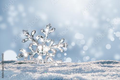 Leinwandbild Motiv Leuchtender großer Eiskristall im Schnee, Bokeh des Winters leuchtet im Hintergrund