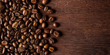 Fototapeta Kitchen - fresh roasted coffee beans on natural dark oak wood panorama wide wooden closeup macro background © stockphoto-graf