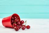 Ripe juicy cherries and copy space. Healthy seasonal cherries in red small bucket. Sweet summer berries.