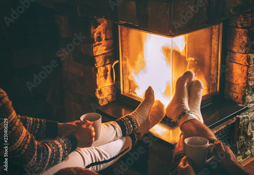 Leinwanddruck Bild Couple in love sitting near fireplace. Legs in warm socks close up image. Cozy Christmas Home atmosphere