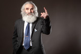 Grandpa with a big beard. An elderly man shows his finger to the top. Gray beard. Beliefs. Gray-haired man.
