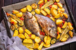 Meal.Baked Dorado fish with vegetables in the oven on a dark background. - 231423612