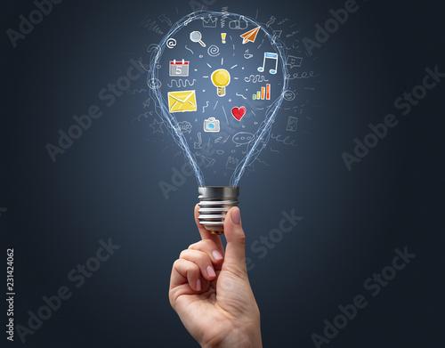 Leinwanddruck Bild Hand holding light bulb on dark background. New apps concept