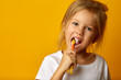 Leinwanddruck Bild - Charming little girl in white t-shirt cleaning teeth with colorful kids toothbrush looking at camera