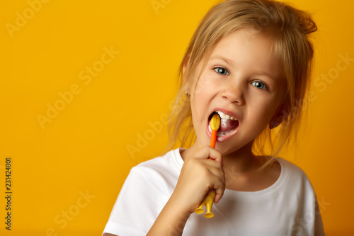 Leinwanddruck Bild Charming little girl in white t-shirt cleaning teeth with colorful kids toothbrush looking at camera