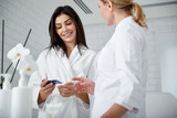 Waist up portrait of smiling woman in soft bathrobe holding sample of face cream and listening cosmetologist - 231427294