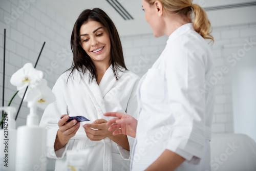 Talia w górę portreta uśmiechnięta kobieta w miękkiej bathrobe mienia próbce twarzy śmietanka i słuchający cosmetologist