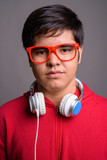 Young Asian teenage boy wearing headphones against gray backgrou - 231429642