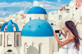 Travel tourist taking phone picture of Santorini Blue dome church, touristic attraction in Europe, European vacation banner. Woman taking smartphone photo of famous destination.