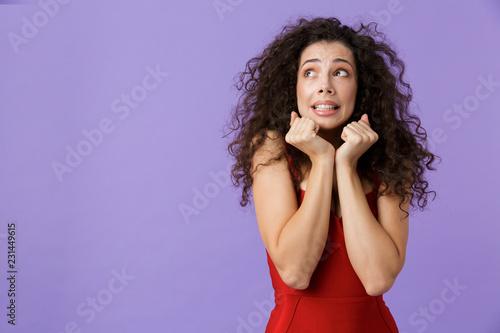 Leinwanddruck Bild Portrait of a scared woman with dark curly hair