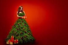 "Постер, картина, фотообои ""Fashion Woman in Christmas Tree Dress, Model hold Xmas Present Gifts over New Year Red Background"""