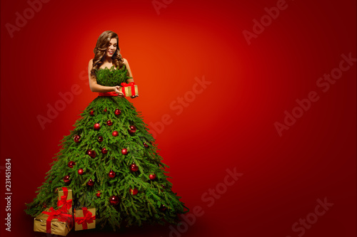 Fashion Woman in Christmas Tree Dress, Model hold Xmas Present Gifts over New Year Red Background - 231451634