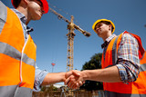 Two men dressed in orange work vests and  helmets shake hands on the building site near the crane - 231454247