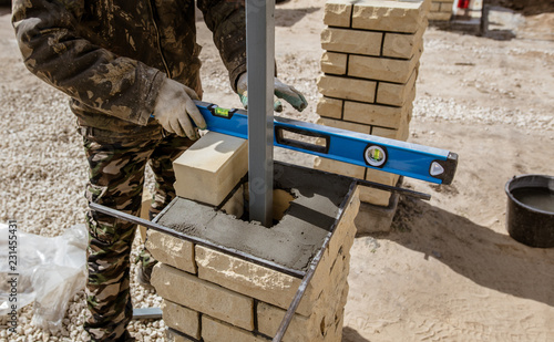The worker is laying bricks on the fence - 231455431