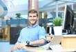 Leinwanddruck Bild - Portrait of happy man sitting at office desk, looking at camera, smiling.