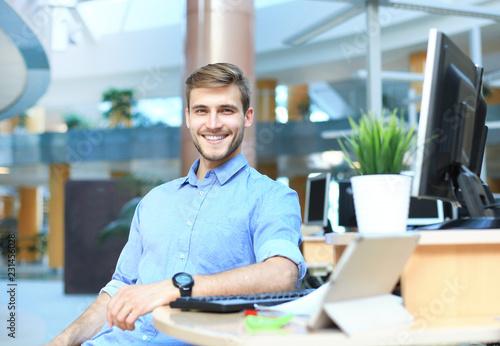 Leinwanddruck Bild Portrait of happy man sitting at office desk, looking at camera, smiling.
