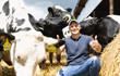happy male farmer on cow farm around herd