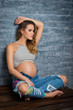 Young woman sitting in top and jeans. Pregnant blonde pending parenthood concept