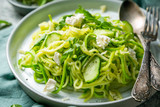 Zucchini noodles with cucumber, feta cheese and arugula, rustic background