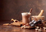 Cocoa with cream, cinnamon, chocolate pieces and various spices. - 231486401