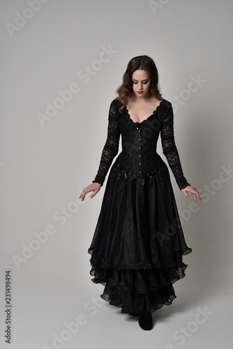 584cdeb8ea full length portrait of brunette girl wearing long black gown with corset.  standing pose on