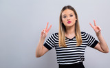 Young woman giving the peace sign on a gray background - 231502857