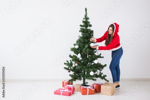 Winter holidays, xmas and people concept - Happy young woman dressed in santa costume decorating Christmas tree in white the room with copy space - 231513026